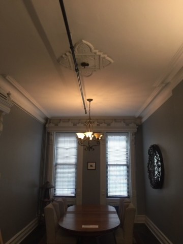 The chandelier was relocated to a position over the Dining Room table and a bronze faceplate was installed over the old box.